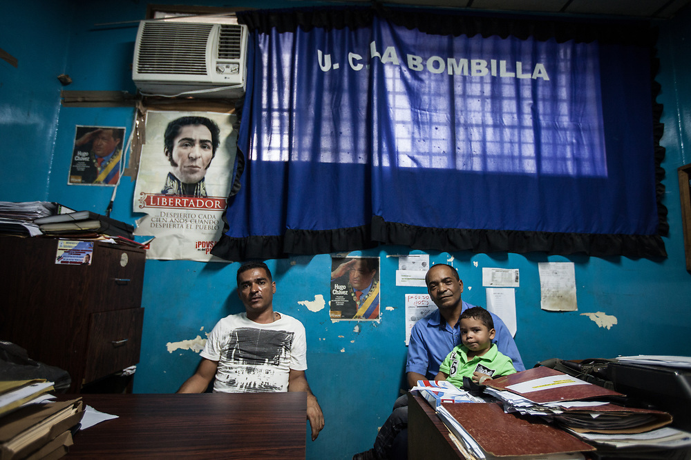 Oscar Gómez, right, bus driver of the 'La Bombilla' transport collective, in San José Petare, Caracas. As well as driving buses, Oscar is the administrator of the collective. Through the government's free programme of adult education he gained a degree in administration and accounting.