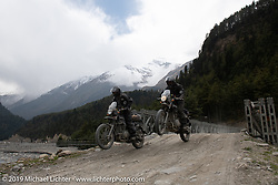 Led Sled's Pat Patterson (L) beside Gary Thomas jumping their Royal Enfield Himalayans during Motorcycle Sherpa's Ride to the Heavens motorcycle adventure in the Himalayas of Nepal. On the fifth day of riding, we went from Muktinath to Tatopani. Friday, November 8, 2019. Photography ©2019 Michael Lichter.