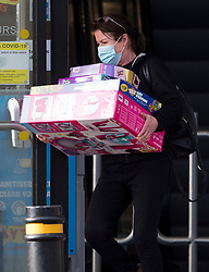 © Licensed to London News Pictures. 03/11/2020. Watford, UK. A woman wearing a face mask, carrying toys from a toy shop in Watford, as shoppers scramble to buy goods before  a second national lockdown comes in to place later this week. Strict measures are due to be re-introduced in an attempt to fight a second wave of the COVID-19 strain of Coronavirus. Photo credit: Ben Cawthra/LNP