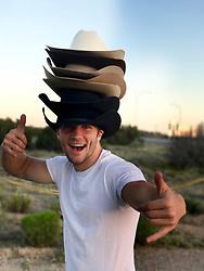 cowboy wearing many cowboy hats outdoors