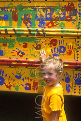 Stock photo of a little girl beside the hand painted school bus