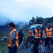 """Mountain Biking on Death Road, Bolivia...A tour group of Mountain Bikers stop to rest and be briefed about the next stage of the journey by their tour leader, biking down infamous narrow dirt road, most of the road no wider than 3.2meter's, is cut into the side of the mountain with sheer drops to the left of up to 600 meter's with virtually no safety rails on the winding steep decent...The North Yugas Road is a 64 Kilometer road leading from La Paz to Corioico. It is legendary for it's extreme danger and in 1995 the Inter American Development Bank christened is as the """"world's most dangerous road"""".. The road was built in the 1930's during the Chaco War by Paraguayan prisoners to connect the Amazon rainforest region of Northern Bolivia to it's capital City La Paz. One estimate is that 200 to 300 travelers were killed yearly along the road. On 24 July 1983, a bus veered off the Yungas Road and into a canyon, killing more than 100 passengers in what is said to be Bolivia's worst road accident..A new stretch of the La Paz-Coroico highroad was opened in 2006 to bypass the notorious stretch known as death road..The danger of the road has now made it a popular tourist destination starting in the 1990's and drawing thrill-seekers and mountain bike enthusiasts who ride on the 64km mainly downhill stretch from La Cumbre, a 4,700 meter peak to Yolosa, a decent of 3600 meter's (11,800 feet). The journey includes breathtaking views of snow covered peaks and towering cliffs and starts along modern asphalted road before entering the jungle itself and the most dangerous and notorious part of the ride. The infamous narrow dirt road, most of the road no wider than 3.2meter's, is cut into the side of the mountain with sheer drops to the left of up to 600 meter's with virtually no safety rails on the winding steep decent..There are now many tour operators catering to this activity, providing information, guides, transport and equipment. Nevertheless, the Yungas Road remains dangerous"""
