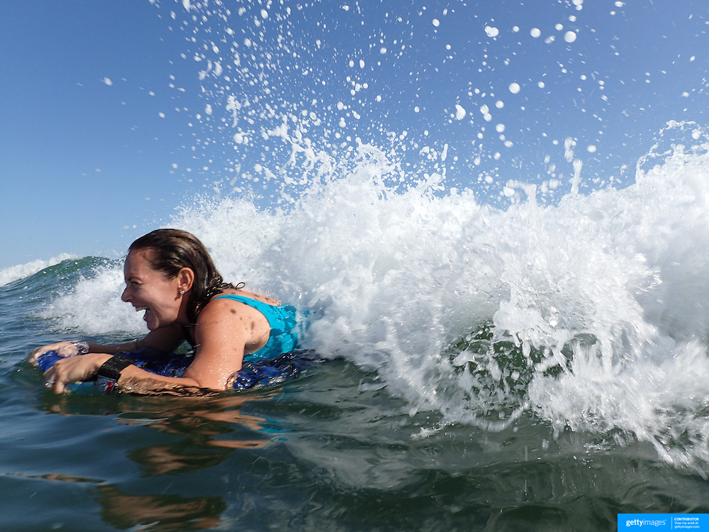 A young adult female catches a wave while surfing on a bodyboard at Cisco Beach, Nantucket, Nantucket Island, Massachusetts, USA. Photo Tim Claytonn