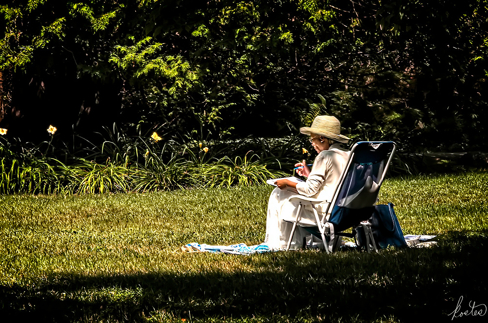 An image of a worman working on papers outdoors in the sunshine, with a large hat & covered up to protect from the sun's rays.