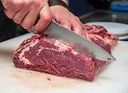 Cheff cuts a beef cut to size
