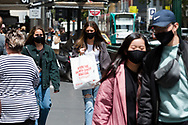 Two woman walk together as shoppers flock back to the CBD during the COVID-19 in Melbourne. With over a week of zero cases in Victoria, Premier Daniel Andrews is expected to make major announcements on Sunday about further easing of restrictions. (Photo by Dave Hewison/Speed Media)