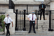 Security guard employees wearing face shields at the National Gallery stand at the bottom of steps leading into a small entrance of the National Gallery during the Coronavirus pandemic, on 29th August 2020, in London, England.