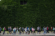 Large group of Chinese tourists pass the famous ivy wall at Horse Guards Parade in London, England, United Kingdom.