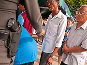 03 JULY 2011 - SAMUT PRAKAN, THAILAND:   A Thai police officer checks voters in Samut Prakan, Thailand, Sunday, July 3. More than 47,000,000 Thais were registered to vote in Sunday's election, which had turned into a referendum on the current government, led, by the Thai Democrats and the oppositionPheu Thai party. Pheu Thai is the latest political incarnation of ousted Thai Prime Minister Thaksin Shinawatra. PT is led by his youngest sister, Yingluck Shinawatra, who is the party's candidate for Prime Minister. Exit polling by three Thai polling firms showed Pheu Thai winning a landslide election.    PHOTO BY JACK KURTZ