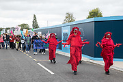 Members of the Red Rebel Brigade join fellow climate activists from Extinction Rebellion at a protest against the expansion of Stansted Airport on 29 August 2020 in Bishops Stortford, United Kingdom. The activists are calling on Manchester Airports Group to withdraw their appeal, for which planning permission was previously refused by Uttlesford District Council, to be able to expand Stansted Airport from a maximum of 35 million to 43 million passengers a year, as well as calling on the Government to halt all airport expansion in order to maintain its commitments under the Paris Agreement.