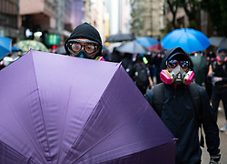 Hong Kong. 6 October 2019. Tens of thousands of pro-democracy protestors march in pouring rain through centre of Hong Kong today from Causeway Bay to Central. Peaceful march later turned violent as a hard-core of protestors confronted police. Pic; Frontline of masked protestors. Iain Masterton/Alamy Live News.