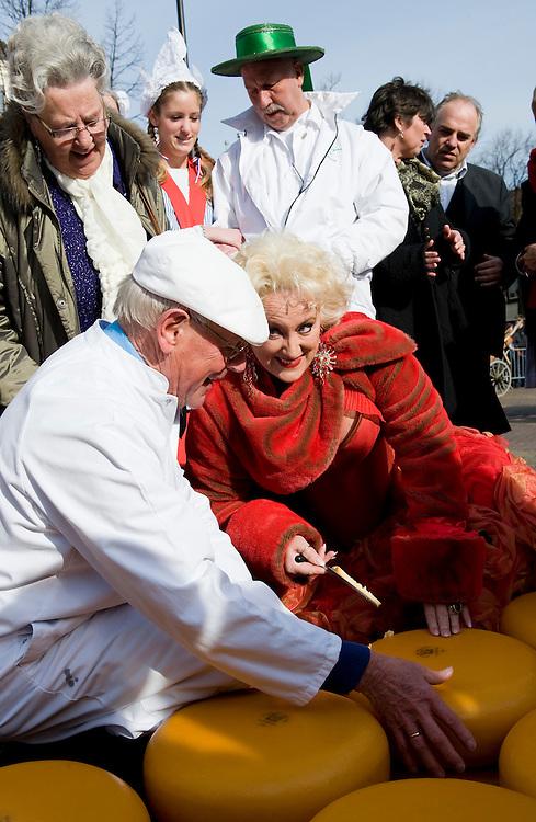 Nederland, Alkmaar, 2 april 2010.Kaasmarkt in Alkmaar. Elke vrijdag vanaf 10 tot 14.00 uur traditionele kaasmarkt met kaasdragers en kaas keuren door keurmeesters..Een kaasmeester keurt een kaas samen met Karin Bloemen. Karin Bloemen steekt een stukje kaas uit..Foto Michiel Wijnbergh