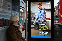 © Licensed to London News Pictures. 10/12/2020. London, UK. A commuter wearing a face covering at a bus stop looks at the COIVD-19 public information campaign digital poster in north London amid fears of London going into tougher lockdown restrictions as early as next week. According to Public Health England, 24 of the London's 32 boroughs recored a rise in infections one week after second lockdown. Photo credit: Dinendra Haria/LNP