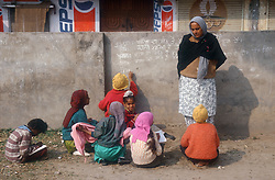 Teacher with school children at primary school in Patiala; Punjab; India; where the children are writing in notebooks and with chalk on a wall,