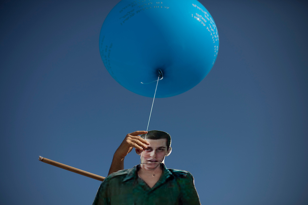 The hand of a supporter of captured Israeli soldier Gilad Shalit is seen as he adjusts a cardboard cut-out bearing Shalit's image, during a demonstration calling for his release outside Prime Minister Netanyahu's office in Jerusalem, on April 17, 2011.