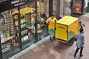 Nederland, Nijmegen, 30-4-2020 Een medewerker van pakketbedrijf DHL levert bestellingen af aan een boekhandel in een winkelstraat. Hij heeft een speciale fiets , vrachtfiets met aanhanger die het bezorgen in de bnnenstad, stadscentrum, voetgangersgebied, autovrije straat, makkelijker maakt . Door de coronacrisis worden er meer online bestellingen gedaan die . Shoppen . Foto: Flip Franssen