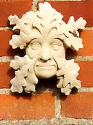 Stone green man face on sale in garden centre, Snape, Suffolk, England, UK