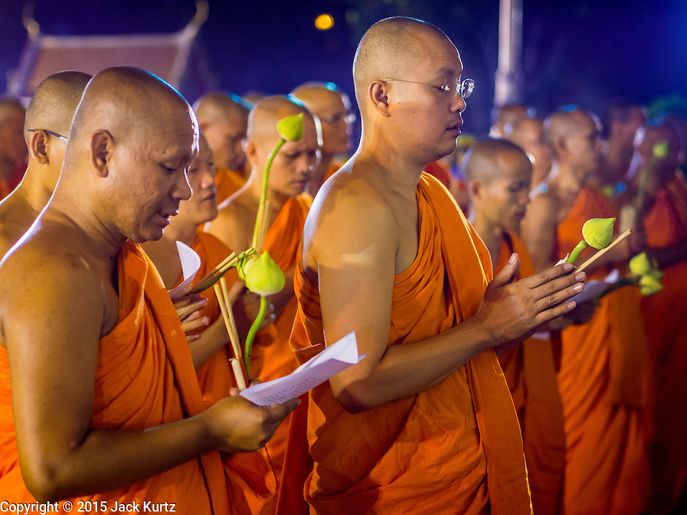 """04 MARCH 2015 - BANGKOK, THAILAND:  Buddhist monks pray in front of the """"wiharn,"""" or prayer hall, at Wat Benchamabophit on Makha Bucha Day. Makha Bucha Day is an important Buddhist holy day and public holiday in Thailand, Cambodia, Laos, and Myanmar. Many people go to temples to perform merit-making activities on Makha Bucha Day. Wat Benchamabophit is one of the most popular Buddhist temples in Bangkok.   PHOTO BY JACK KURTZ"""