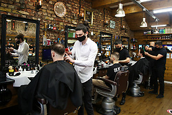 © Licensed to London News Pictures. 12/04/2021. London, UK. Men get their hair cut in a barbers on Green Lanes in Haringey, north London, which reopens after 4 months of Covid-19 lockdown. Cafes, restaurants, pubs, non-retail business and hairdressers across the UK closed following third national lockdown on 6 January, after a surge of coronavirus infections and hospital admissions across the UK. As restrictions are eased, cafes, restaurants, pubs, non-retail business and hairdressers reopen today.<br /> Photo credit: Dinendra Haria/LNP