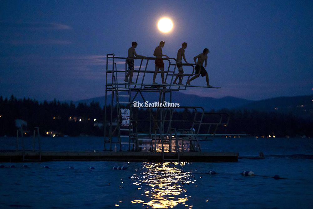 Swimmers jump off the diving board at Madison Park Beach on Lake Washington in Seattle. (Erika Schultz / The Seattle Times)