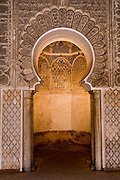 Elaborate arched alcove inside the Ali ben Youssef Medersa in the Marrakech medina, Morocco.