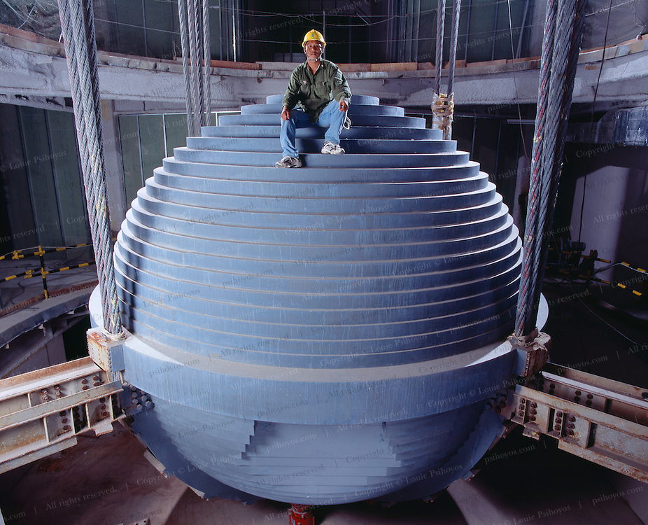 The 730 ton tuned mass damper hanging over four floors in the 80's equals out the movement of the building during earthquakes and typhoons.  In a bold design move the architects decided to leave the damper exposed over the various levels which will become restaurants.