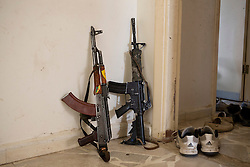 © Licensed to London News Pictures. 28/09/2014. Al-Yarubiyah, Syria. A Chinese made Kalashnikov and American M4 rifle lean against a wall in a building occupied by Syrian Kurdish YPG fighters in Al-Yarubiyah, Syria.<br /> <br /> Facing each other across the Iraq-Syria border, the towns of Al-Yarubiyah, Syria, and Rabia, Iraq, were taken by Islamic State insurgents in August 2014. Since then The town of Al-Yarubiyah and parts of Rabia have been re-taken by fighters from the Syrian Kurdish YPG. At present the situation in the towns is static, but with large exchanges of sniper and heavy machine gun fire as well as mortars and rocket propelled grenades, recently occasional close quarter fighting has taken place as either side tests the defences of the other. Photo credit: Matt Cetti-Roberts/LNP
