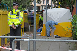 © Licensed to London News Pictures 30/07/2021. Greenwich, UK. First crime scene outside Stanton House flats near a playground for children. A police investigation has been launched after a double stabbing in Greenwich, London which has left on man dead and another in a life-threating condition in hospital. A large cordon is in place with police forensic officers working three crime scenes near the Cutty Sark. Photo credit:Grant Falvey/LNP
