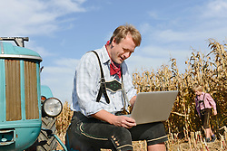 Farmer with laptop on field with tractor, his son playing in background, Bavaria, Germany