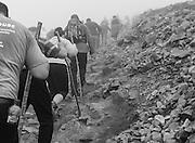 Climbers struggle up the steep grade nearing the summit.