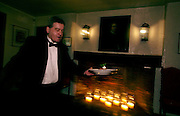 Newport, RI - waiter rushes past fireplace and an old portrait in the oldest colonial tavern and inn in the country, the White Horse Tavern.