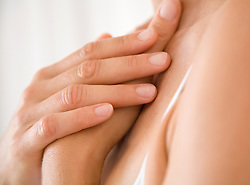 Extreme close up of woman's hands resting on chest