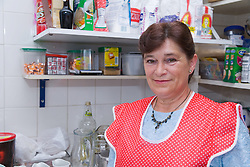 Cook standing in front of shelf stacked with cooking ingredients in kitchen of Polish Social Club,