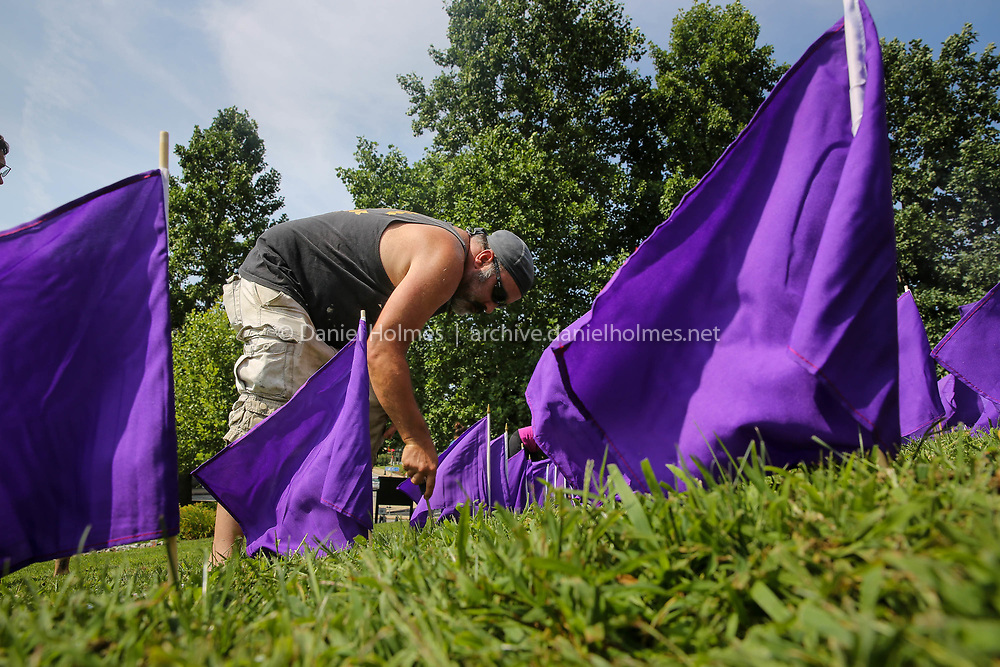 (8/25/18, MARLBOROUGH, MA) Lenny MacGregor, of Marlborough, places flags for those who have died of an opioid overdose at the Walker Building in Marlborough on Saturday. [Daily News and Wicked Local Photo/Dan Holmes]