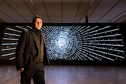 "© Licensed to London News Pictures. 21/11/2019. LONDON, UK.  American artist Leo Villareal poses by his work ""Detector"", 2019, at a preview of his first solo exhibition at Pace gallery in Mayfair.  The works use LED lights and custom software to produce moving abstract image in a show which runs 22 November to 18 January 2020.  This exhibition coincides with the recent launch of Illuminated River, Villareal's major public artwork that will illuminate 14 bridges along the River Thames.  Photo credit: Stephen Chung/LNP"