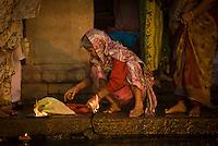 An old woman prepares her offering during the festival of Kartik Poornima in Varanasi, Uttar Pradesh, India