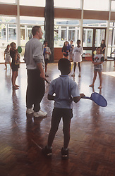 Junior school pupils taking part in sports game during indoor PE lesson,