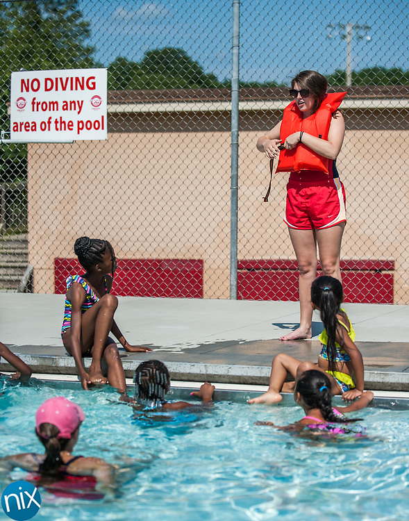 Lifeguard Katherine Barnett shows children from the Logan Day Care Center how to put on a life vest during a special swim lesson put on by Safe Kids Cabarrus at the McInnis Aquatics Center in Concord Friday morning. A grant from Speedway Children's Charities helped fund the swim lessons where the children aged 4-10, learned how to swim along with general water safety