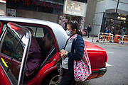 A women with face mask waits next to a taxi in Central district.