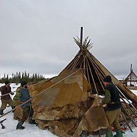 North of the Arctic Circle in Russia, members of the last nomadic Komi reindeer herding clan wrap their chum (tepee) with a carefully-sewn patchwork of reindeer skins. Over this, they will place a layer of canvas.