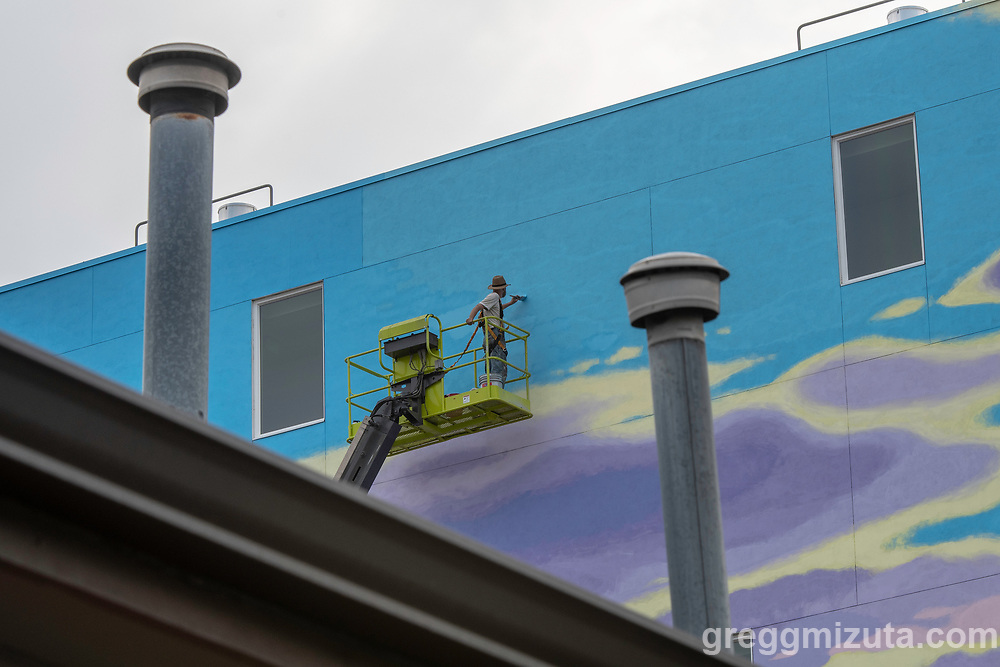 Portland, Oregon-based artist David Carmack Lewis works on his mural on west side of The Fowler in Boise, Idaho on August 11, 2018.<br /> <br /> Lewis started the mural on July 21 and finished it on August 15th. The mural covers approximately 40 percent of the building closest to Myrtle Street, and works its exterior features like windows into a stylized depiction of the Boise Foothills against a partly cloudy sky.