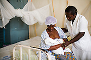 Nurse Esther Bonsu helps Florence Andoff breast feed her 1-day-old boy at the La Polyclinic in Accra, Ghana on Tuesday June 16, 2009.