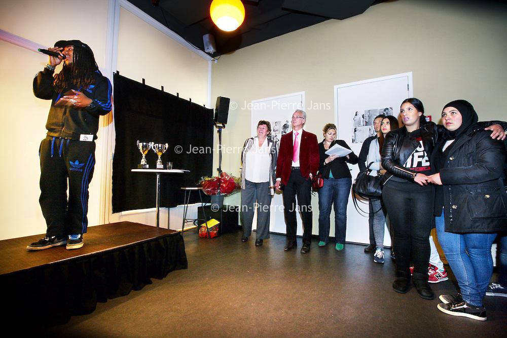 Nederland, amsterdam , 15 april 2014.<br /> Steeds meer jongeren hebben flinke schulden. In Slotermeer wordt hier actie op ondernomen en de jongeren uit de buurt werken hier aan mee. Samen met jongeren worden zes filmpjes gemaakt die precies uitleggen hoe schulden te voorkomen zijn.<br /> Gerzon Soenarto is één van de jongeren die aan de films meewerkte, treedt tijdens de premiere live op onder zijn artiestennaam 'Gizza'. Hij zat zelf in de schulden en heeft een rap gemaakt om zijn leeftijdsgenoten te waarschuwen voor de gevolgen hiervan. Gerzon deed ook diverse interviews voor de films.<br /> Op de foto: Gerzon rapt terwijl het publiek naar het promofilmpje kijkt tijdens de première plaats van de filmpjes 'Hoe word je rijk in Slotermeer?' in Coffeemania aan de Slotermeerlaan.<br /> Foto:Jean-Pierre Jans