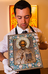 Sotheby's, London, November 21st 2014.  Sotheby's presents one of its strongest offerings of Russian paintings, icons and artworks as the renowned fine art  auction house celebrates its 25th year in Russia. Pictured: A gallery technician  holds a silver-gilt and cloisonne enamel icon of St Nicholas the Miracleworker, expected to fetch between £50,000 - 70,000 at auction.