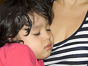 close up of child resting against mothers breast