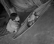 A small village outside Pursat.  Chnin Sokhak, 25, stacks firewood for cooking, rocks her son, Heng Nari, in a hammock.