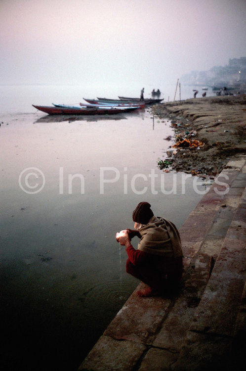 Man makes offering to the Ganges, Holy city of Varanasi, India