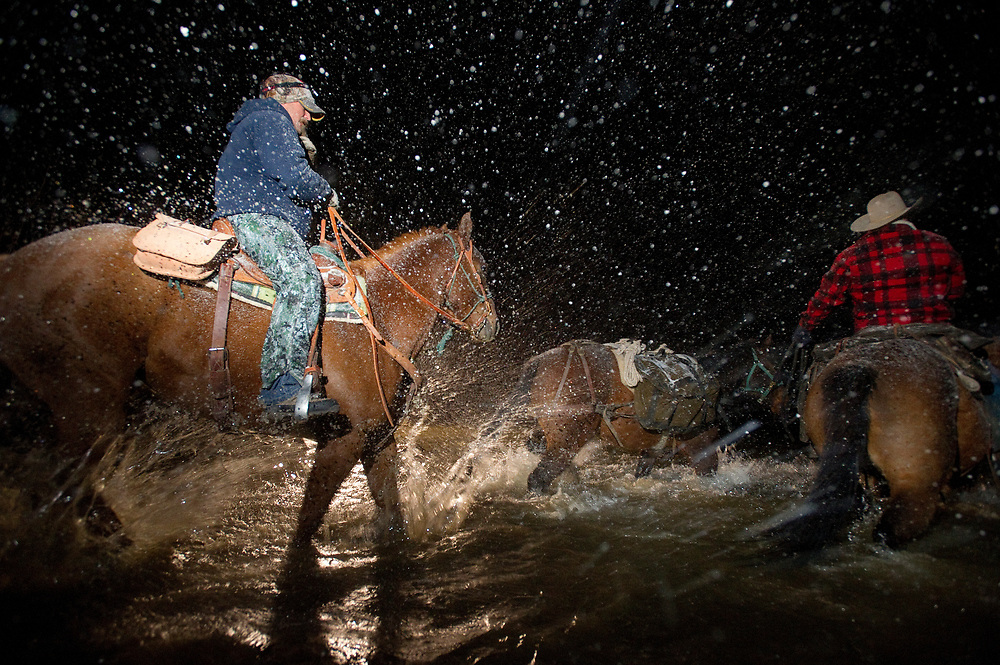PRICE CHAMBERS / NEWS&GUIDE<br /> Splashing through the shallow Gros Ventre River near the Kelly jumping cliffs, horsemen head into the night in search of shed elk antlers that would soon be covered by snow.