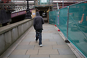 """Man wearing his trousers slung low, struggles to keep them up. London, England, UK. Sagging is a manner of wearing trousers or jeans which sag so that the top of the trousers or jeans are significantly below the waist, sometimes revealing much of the underwear. Sagging is predominantly a male fashion. In some countries this practice is known as """"low-riding"""". The style was popularized by hip-hop artists in the 1990s. It later became a symbol of freedom and cultural awareness among some youths or a symbol of their rejection of the values of mainstream society. It is often claimed the style originated from the United States prison system where belts are sometimes prohibited."""