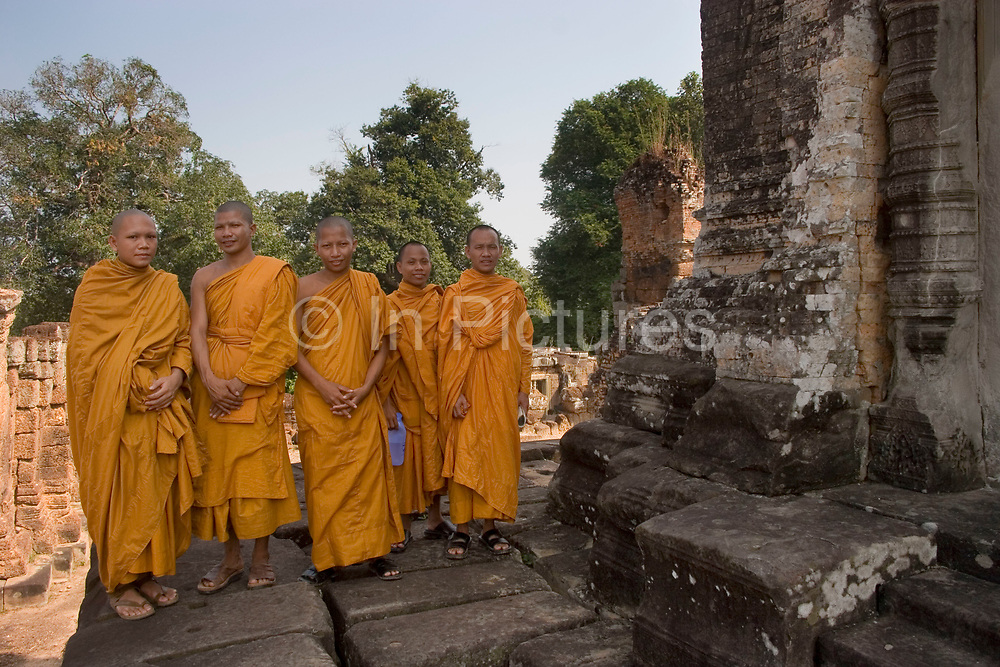 Young Buddhist monk Ronrom (20 left) with colleagues, at East Mebon where he and his colleagues and venerable teachers have come for the day. Based at the nearby Pradaet Pagoda, his learning of Buddhism will last for ten years. East Mebon. Built in 953 for King Rajendravarman's parents, the original temple was surrounded by water so approached by boat. The sandstone towers at the summit are in the Pre Rup style.